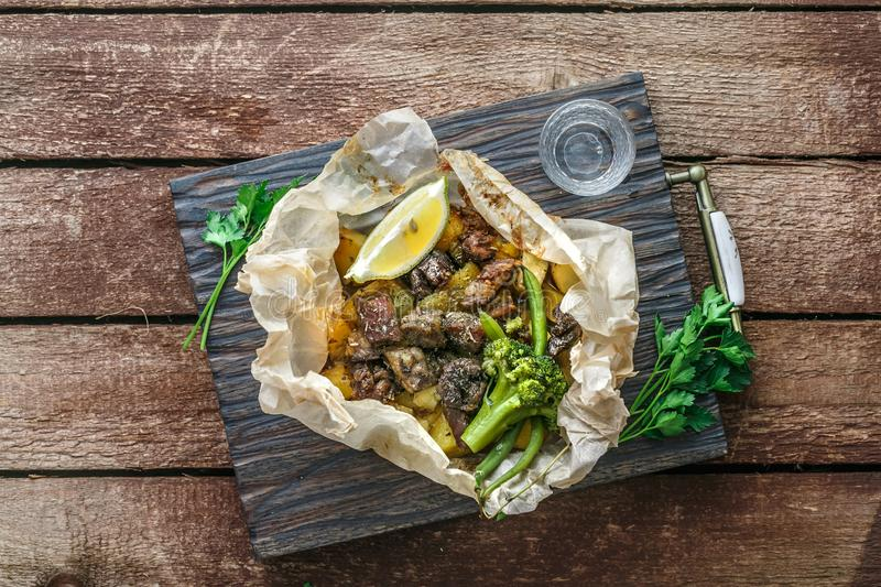 Lamb kleftiko, potato and vegetables served on wooden cutin board, rustic style stock photos