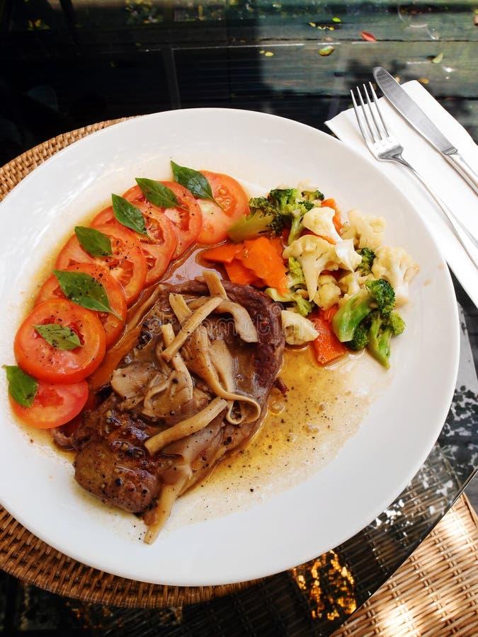 Lamb kotletter med grönsaker - utomhus- äta middag arkivfoton