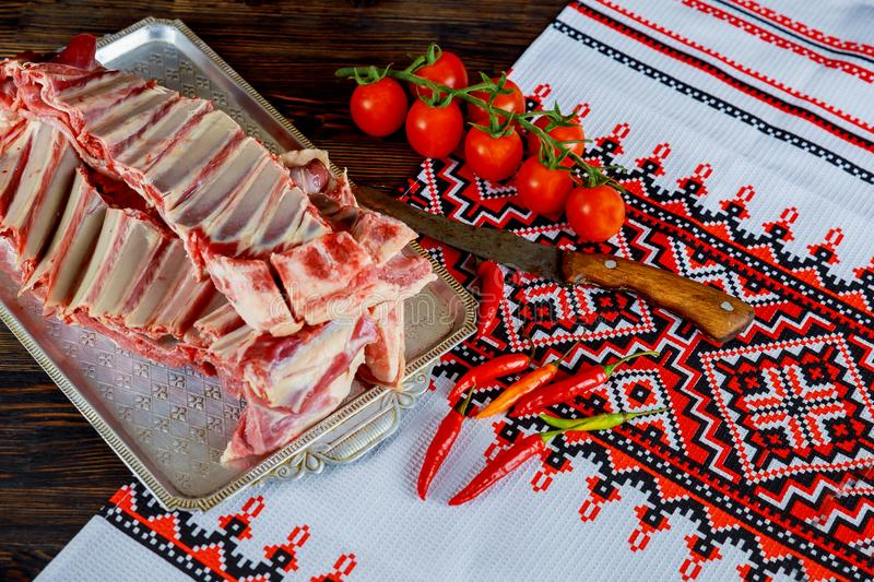 Lamb mutton with spices, red pepper and garlic bulbs on slate and wooden table. Top view stock photo