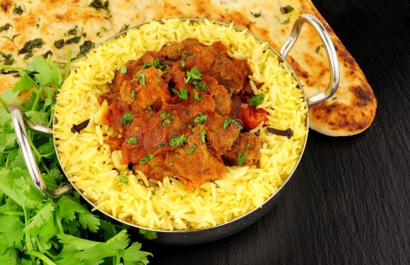 Lamb Rogan Josh Curry With Naan Bread. Lamb rogan josh curry meal with pilau rice and naan bread stock photo