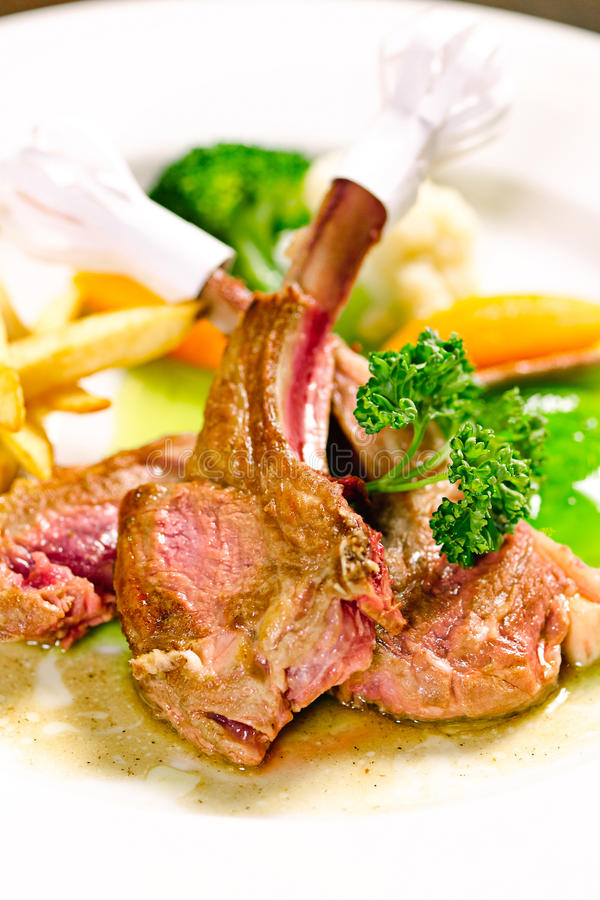Medium rare rib lamb steak isolated. On dish stock photo