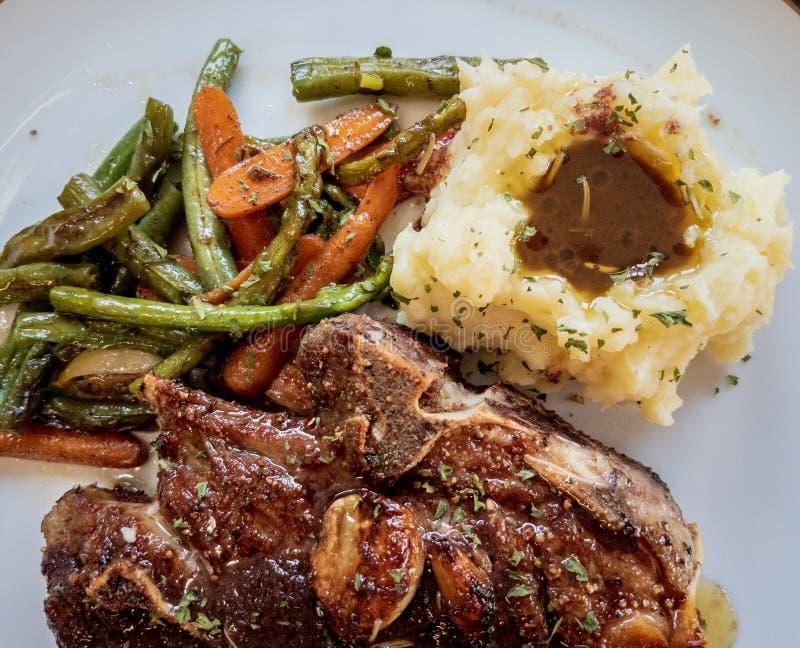 Lamb Steak met gehakte aardappelen en groenten royalty-vrije stock afbeeldingen
