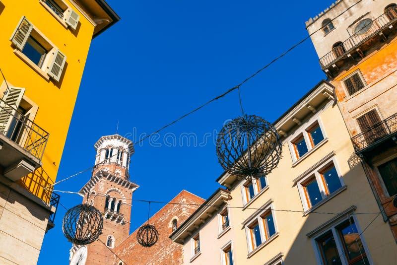 Lamberti torn i den Verona Torre deien Lamberti och omgeende färgrika hus i centret Härlig blå himmel, vintertid royaltyfria bilder