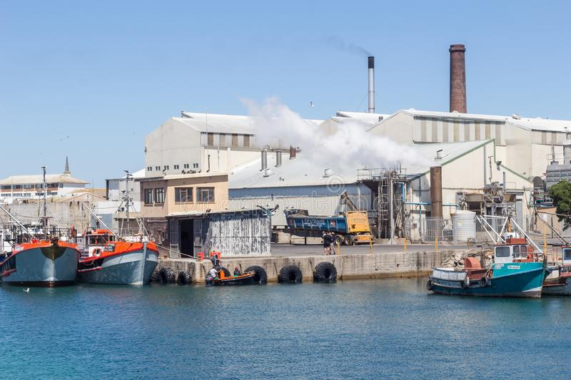 Lambert`s bay harbour with fishing vessels and factory with processing plant chimneys stock image