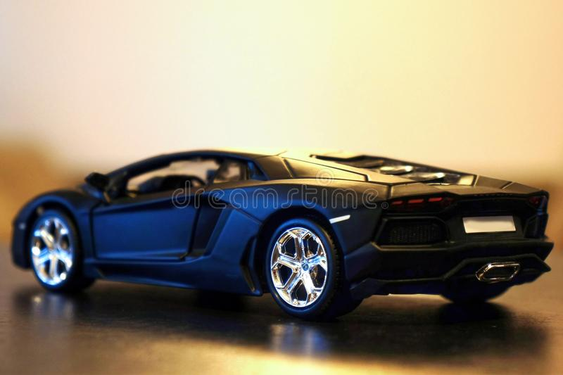 Lamborghini Aventador LP700-4 model car lateral/rear. Lamborghini Aventador LP700-4 die-cast metal model toy 1:24 scale, Black. Lateral / rear view royalty free stock images