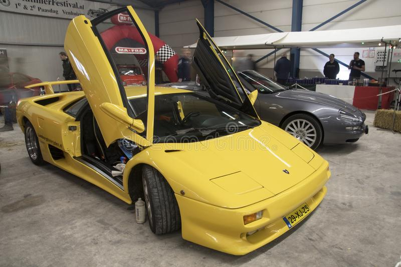 VENHUIZ Bright yellow Lamborghini sports with an open door. The Lamborghini Diablo is a high-performance mid-engine sports car that was built by Italian stock photos
