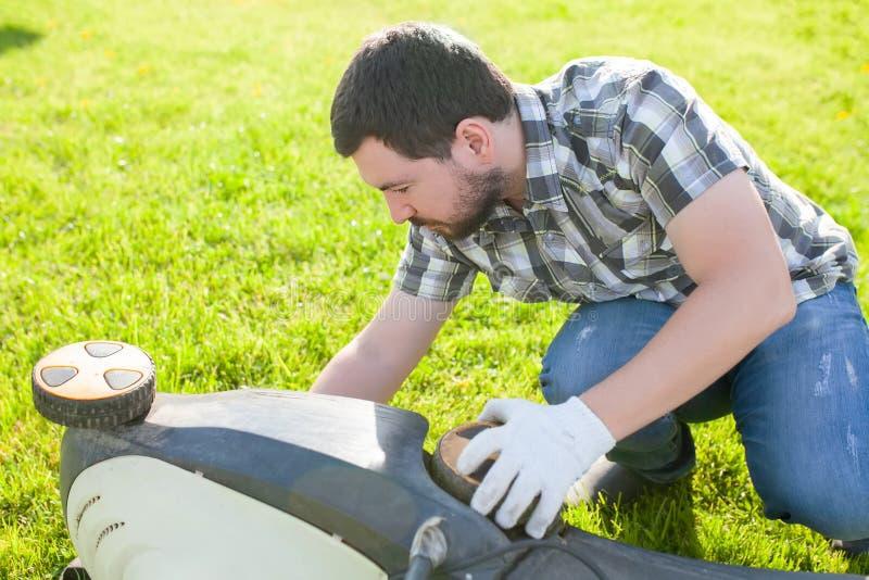 Lame de tondeuse à gazon de nettoyage ou de réparation d'homme image stock