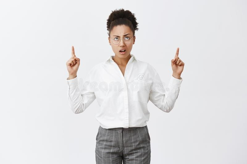So lame. Portrait of unimpressed displeased and disappointed african-american female entrepreneur in glasses and pants. Frowning, pointing and staring stock photo