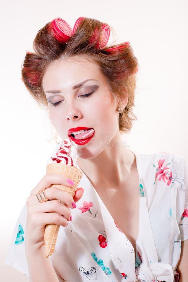 Lamedura del postre: la mujer joven hermosa atractiva que come el cono de helado observa cerrado aislado sobre el fondo blanco de imagenes de archivo