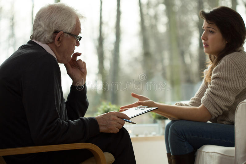 Lamenting woman. Young women lamenting to her elderly psychologist stock photos