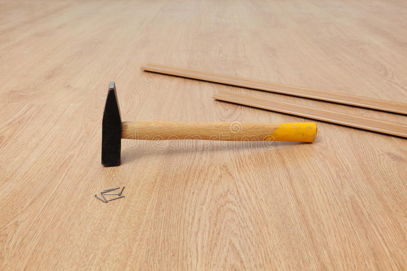 Laminate flooring of room. Closeup of hammer, nails and batten for laminate floor, floating wood tile royalty free stock photography