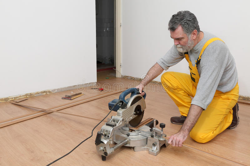 Laminate flooring of room. Worker cut wooden batten for laminate floor, floating wood tile stock images
