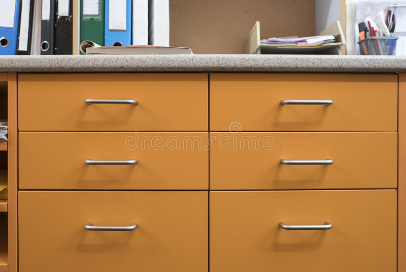 Laminated Drawers in Office. Mustard drawers with streamline metal handles and marble laminated top in an office royalty free stock image