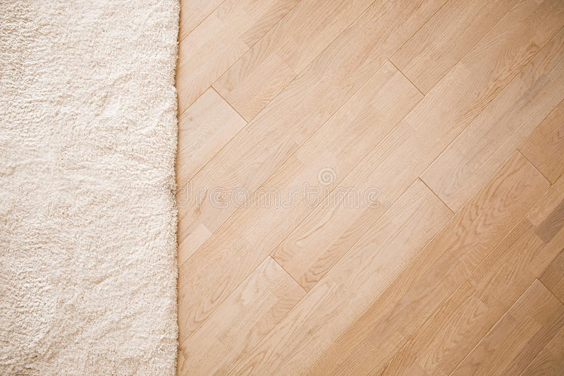 Laminatparquetegolv med beige mjuk matta royaltyfri bild
