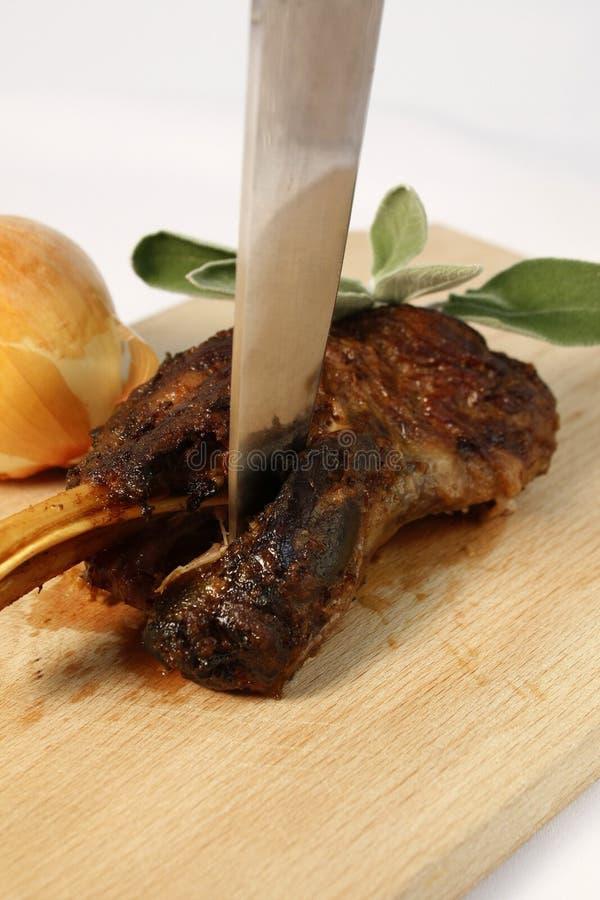 Lamm Bein, dasbraten gekocht verlangsamen, zeigte auf hölzernem Schneidebrett mit großem Messer, Zwiebel und frischen tadellosen  stockfoto