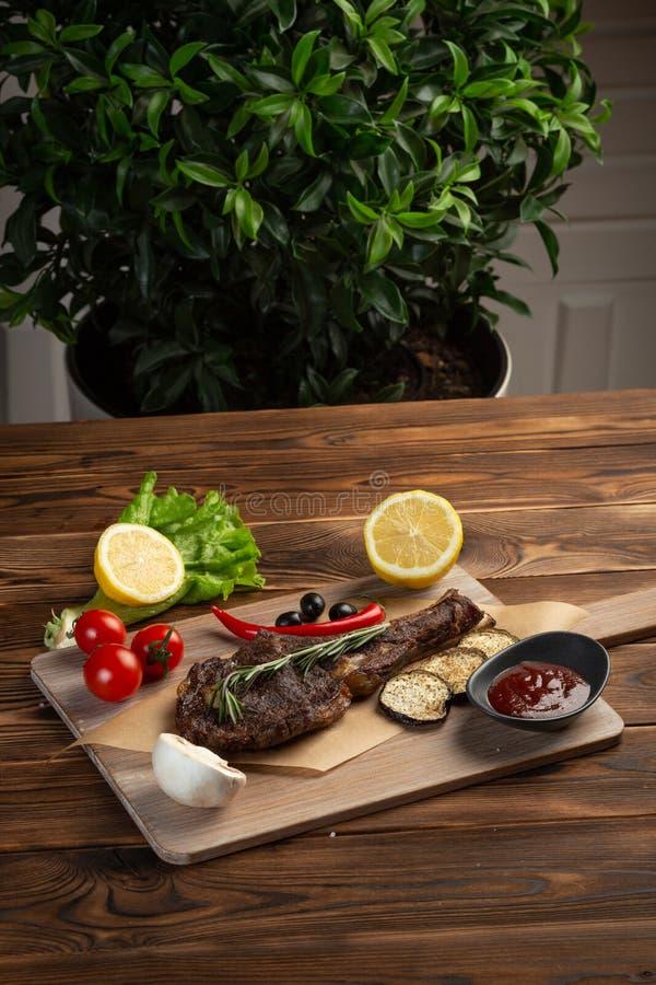 lammbiff med grönsaker och tomatsås på en mörk träbakgrund royaltyfria foton