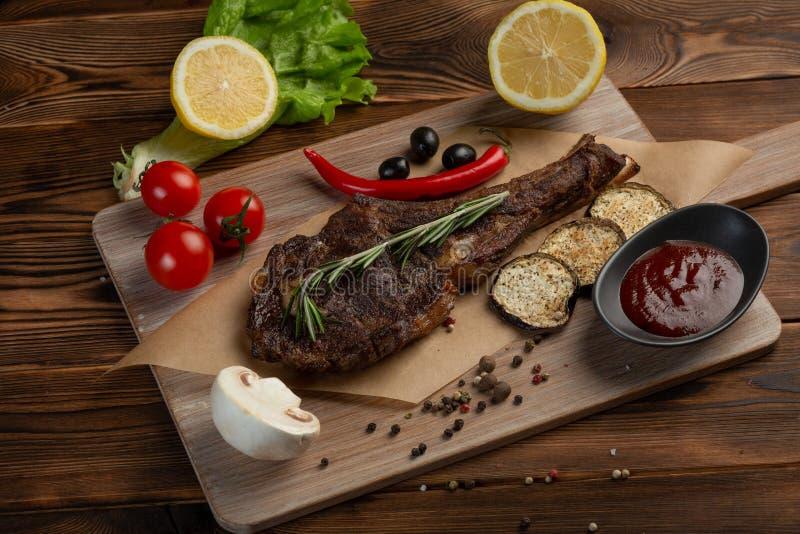 Lammbiff med gr?nsaker och tomats?s p? en tr?bakgrund arkivfoto