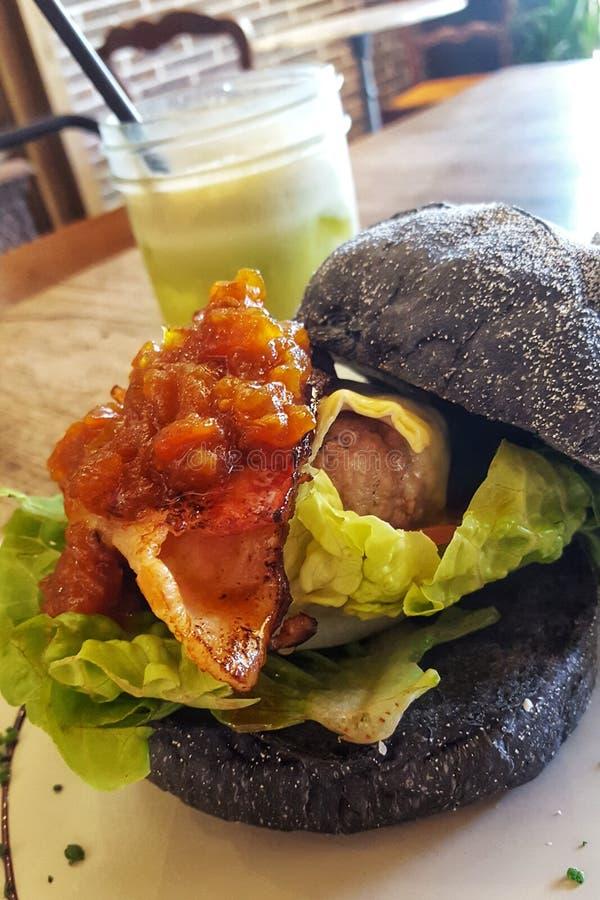 Lammhamburgare med tomatnjutningen, den smältta brien och frasig bacon på en kolbulle, med en grön smoothie royaltyfri foto