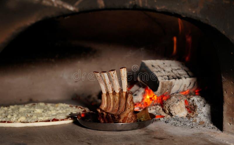 Lammkarree und oizza im Ofen lizenzfreie stockfotografie