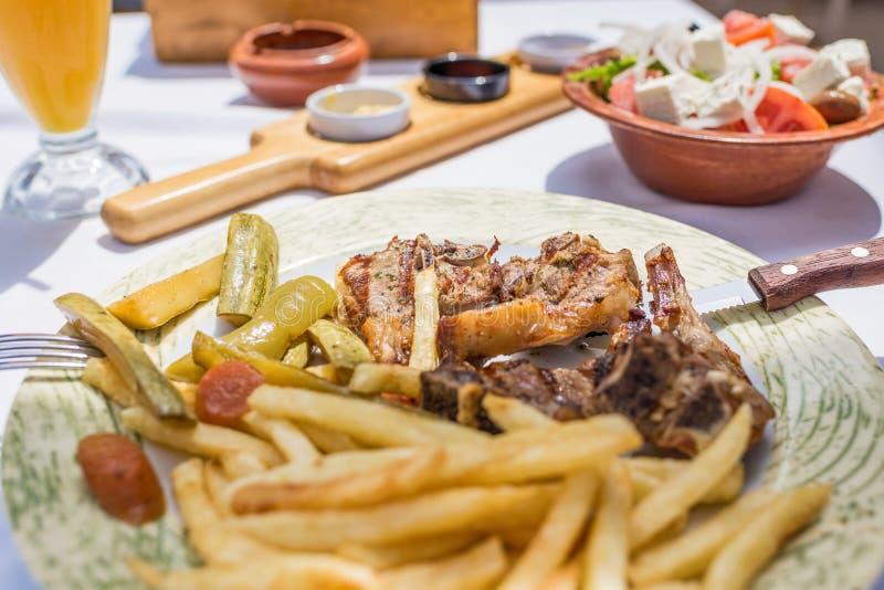 Lammkotletter med grönsaker och stekpotatisar på en platta i en grekisk restaurang eller krog royaltyfri fotografi