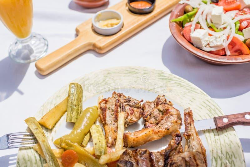 Lammkotletter med grönsaker och stekpotatisar på en platta i en grekisk restaurang eller krog royaltyfria foton