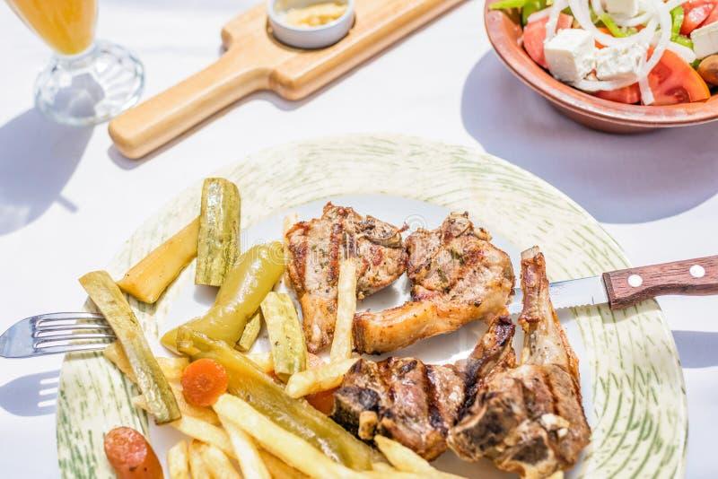 Lammkotletter med grönsaker och stekpotatisar på en platta i en grekisk restaurang eller krog royaltyfria bilder