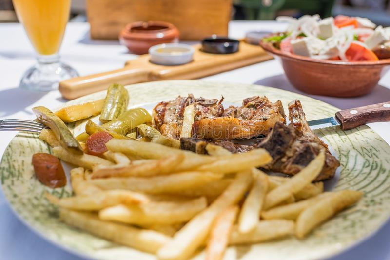 Lammkotletter med grönsaker och stekpotatisar på en platta i en grekisk restaurang eller krog arkivfoto