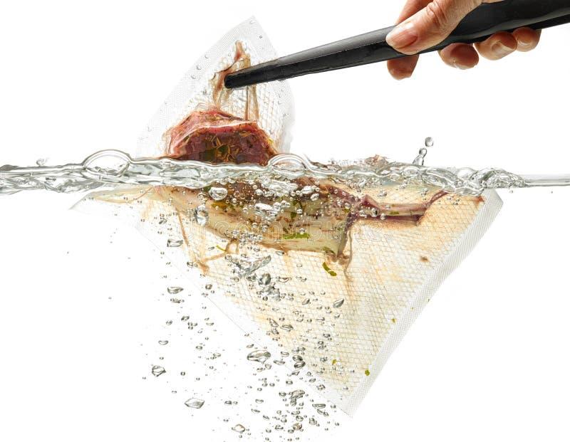 Lammrippen im Vakuumbeutel im Wasser; lokalisiert auf Weiß lizenzfreies stockbild