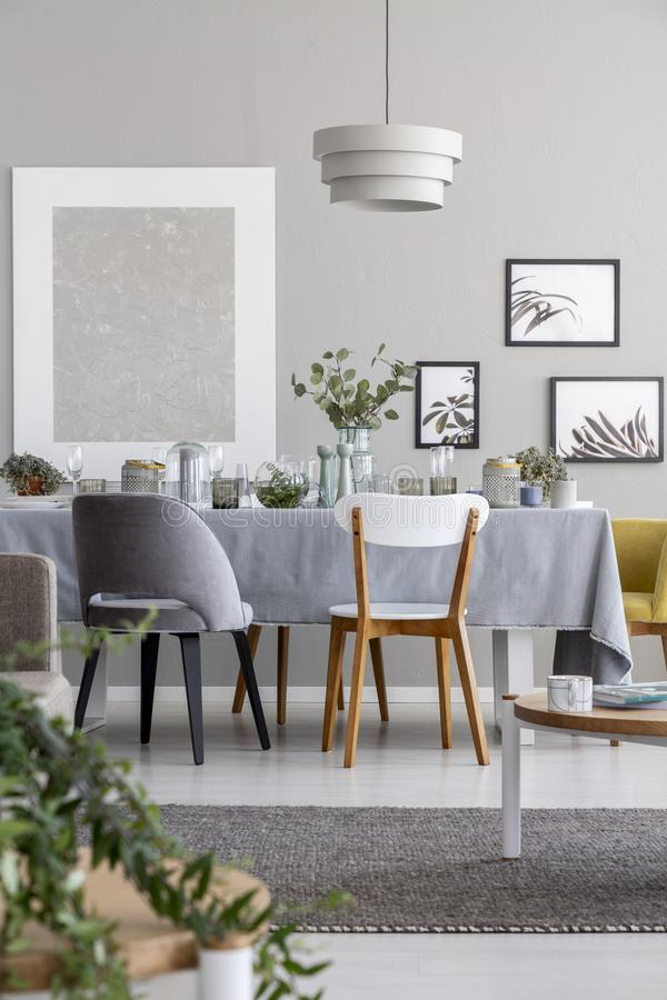 Lamp above chairs and table in grey dining room interior with mockup and posters. stock images