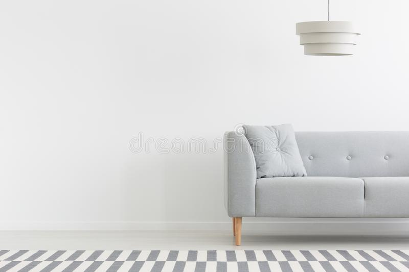 Grey couch in white minimal apartment interior with copy space on empty wall. Real photo. Lamp above grey couch in white minimal apartment interior with copy stock image