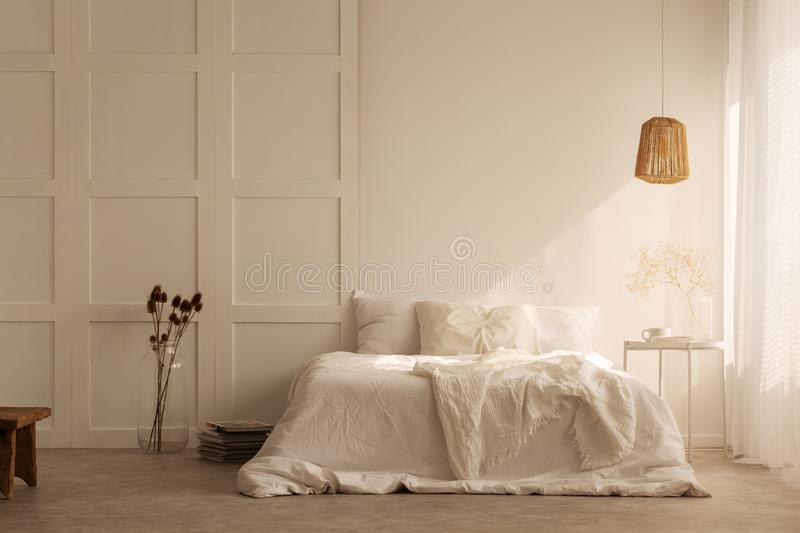 Lamp above white bed with pillows in minimal bedroom interior with plants and stool stock images
