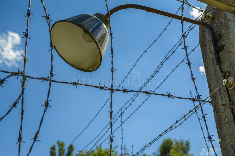 Lamp on barb wire fence stock photography