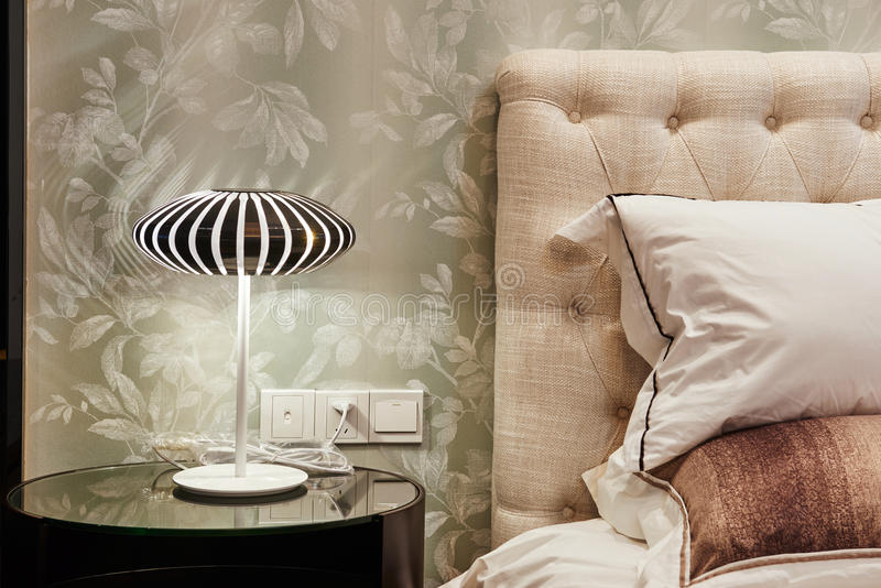 Lamp on bedside table in bedroom. Fashionable modern lamp on bedside table in bedroom royalty free stock photography