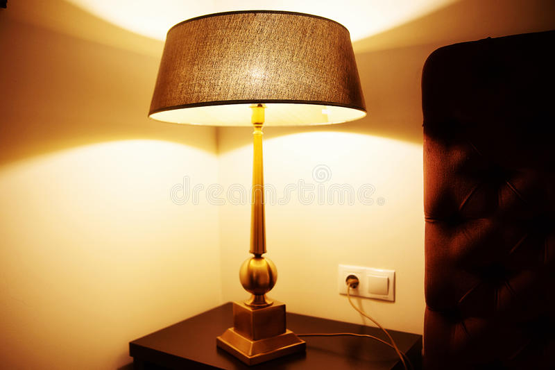 Lamp on the bedside table. Photo of lamp on the bedside table royalty free stock images