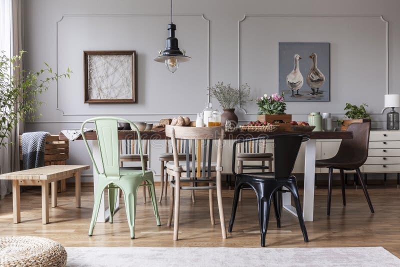 Lamp boven houten lijst met bloemen in modern grijs eetkamerbinnenland met stoelen Echte foto royalty-vrije stock foto