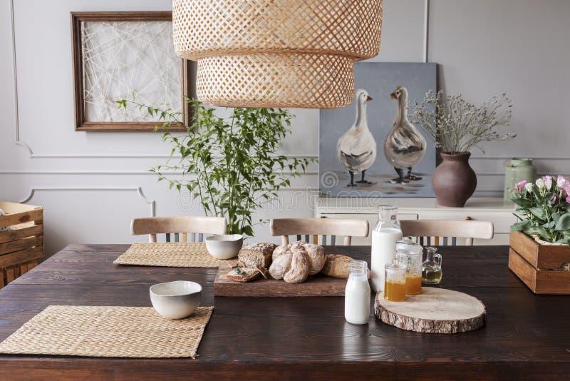 Lamp boven houten lijst met voedsel en kommen in grijs eetkamerbinnenland met affiches Echte foto royalty-vrije stock foto