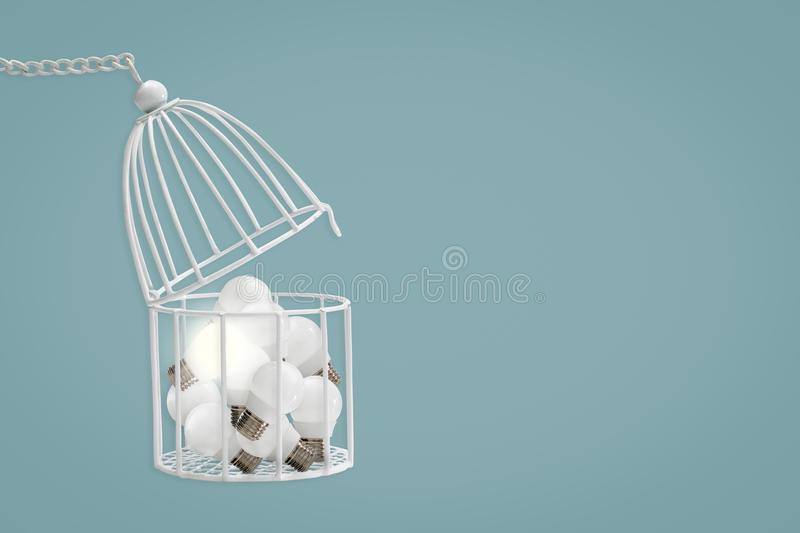 Lamp bulb in white bird cage isolated on blue background, minima royalty free stock image