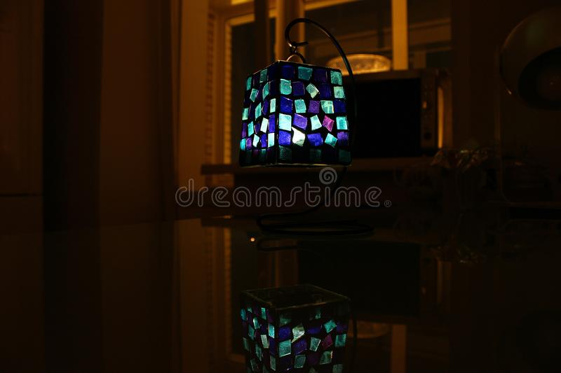 Lamp with a candle inside on a table royalty free stock image