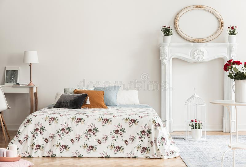 Lamp on desk next to patterned bed with pillows in white bedroom royalty free stock image