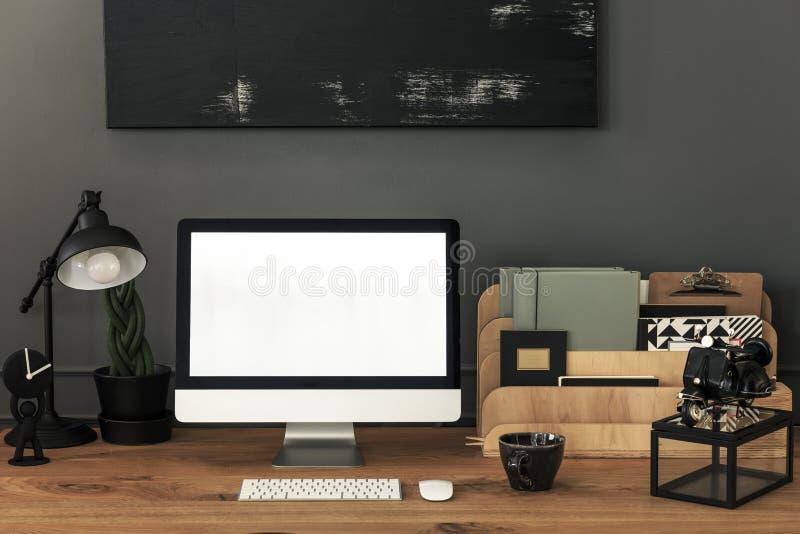 Lamp en organisator op houten bureau in het grijze binnenland van het huisbureau met model Echte foto stock fotografie