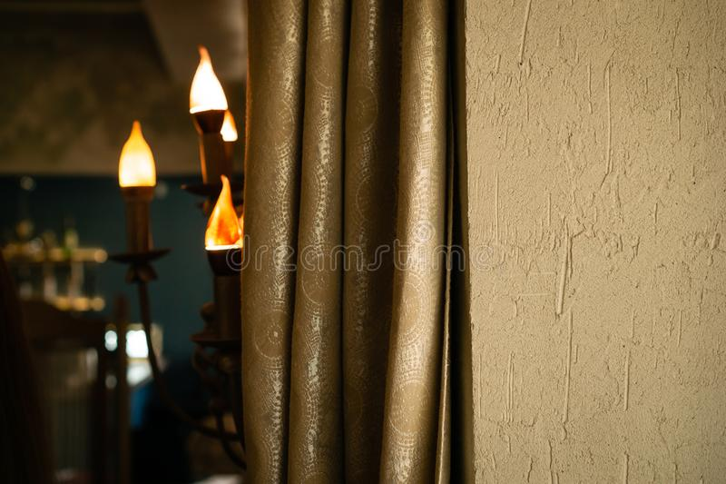 Lamp in the form of candles on the wall. Blurred backdrop. royalty free stock image