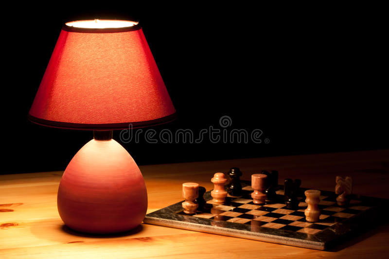 Lamp illuminating chess-board stock image