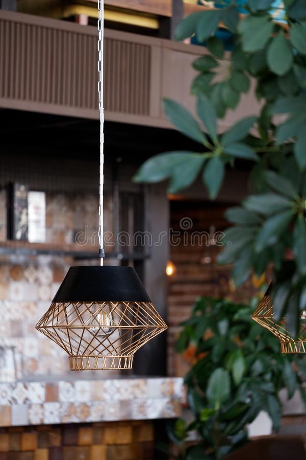 Lamp in the interior of the cafe. On the background of plants stock images