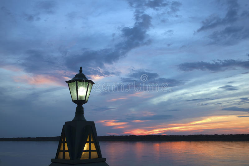 Lamp lights up by the river stock image