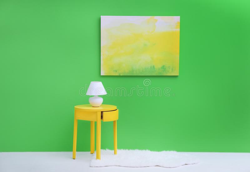 Lamp on little yellow table near wall. Lamp on little yellow table near green wall stock images