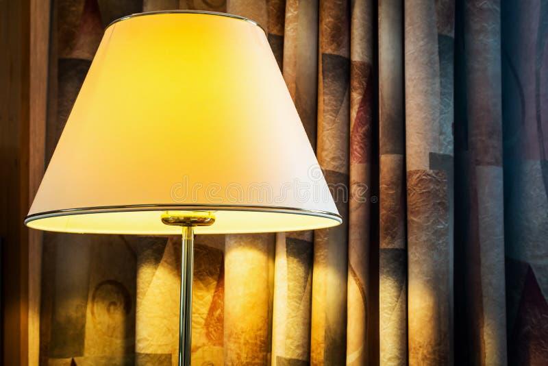 Lamp met zacht geel licht op de achtergrond van gordijnen royalty-vrije stock fotografie