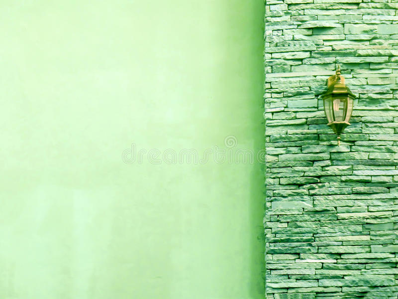 Lamp in middle light green ancient stone pieces wall at right an. D smooth wall at left royalty free stock photo