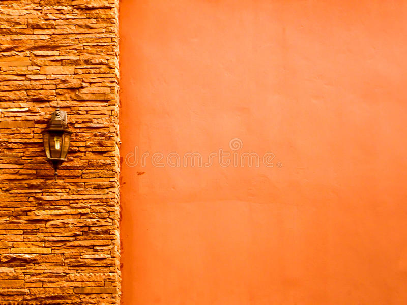 Lamp in middle orange ancient stone pieces wall at left and smooth wall at right royalty free stock images