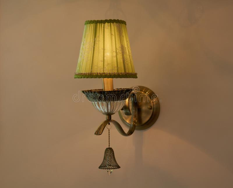 Lamp mounted on the wall. Old style lamp mounted on beige wall with lampshade stock photos