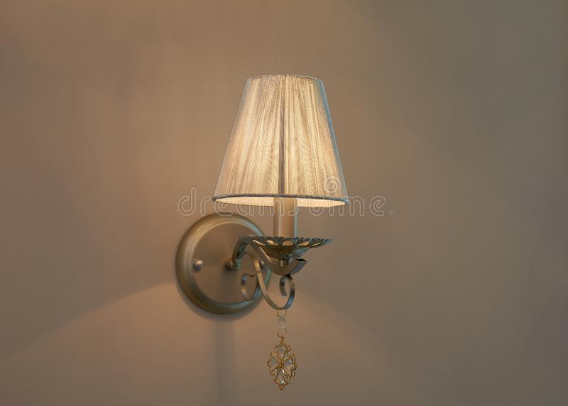 Lamp mounted on the wall. Old style switched on lamp mounted on beige wall with lampshade royalty free stock photos